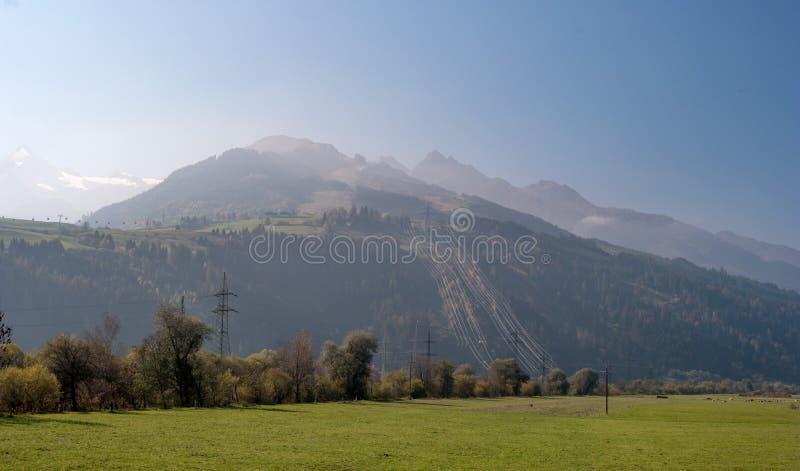 奥地利阿尔卑斯早晨 塔与留下山的许多的输电线导线 在山的轻的雾 在 免版税库存图片
