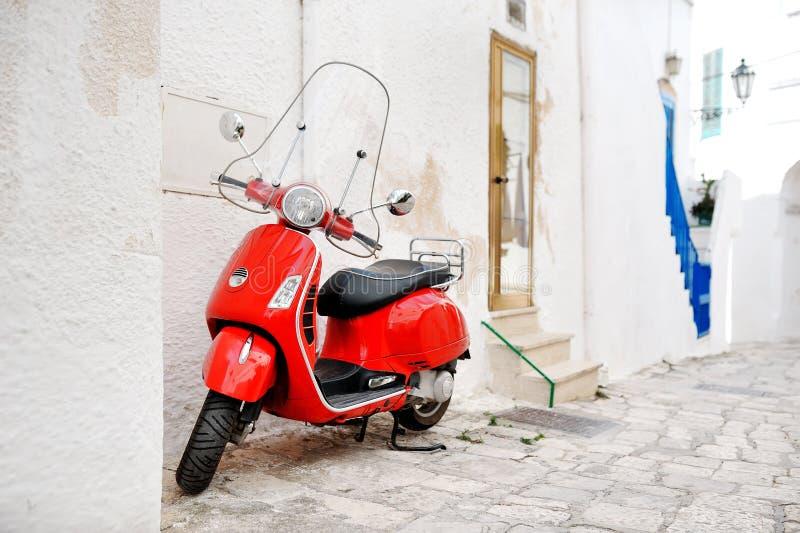 奥斯图尼,普利亚,意大利-红色滑行车在巷道 免版税图库摄影
