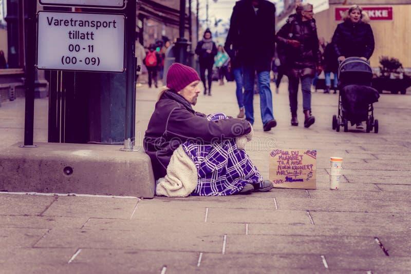 奥斯陆,挪威- 2018年3月, 26日:坐在地面的室外观点的未认出的无家可归的人请求在的金钱 库存照片
