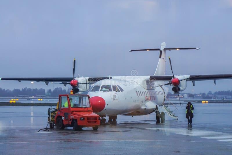 奥斯陆/挪威- 2018年11月30日:Wideroe在跑道的螺旋桨推进式飞机有离去的货物卡车的到罗弗敦群岛海岛 库存图片