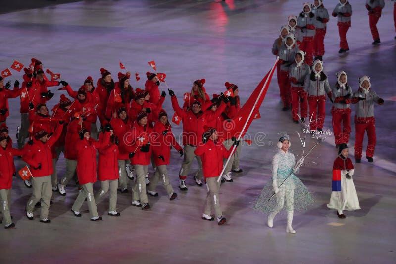 奥林匹克冠军举着瑞士的旗子的达廖・科洛尼亚带领瑞士奥林匹克队在2018个冬季奥运会 免版税库存照片