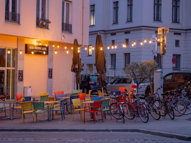 奥格斯堡,德国- 2019年5月5日:与五颜六色的椅子、桌和光的室外arragement从酒吧Beim Weissen 库存图片