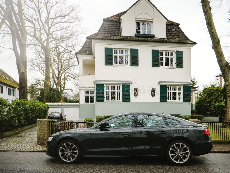 奥迪A8黑色汽车在现代房子附近停放了 免版税图库摄影