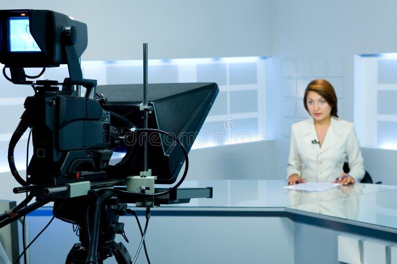 女主持人现场直播的电视 免版税库存照片