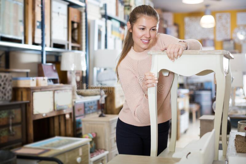 女买家站在床头柜附近 免版税库存图片