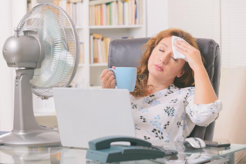 女人在办公室或家里受热 库存图片