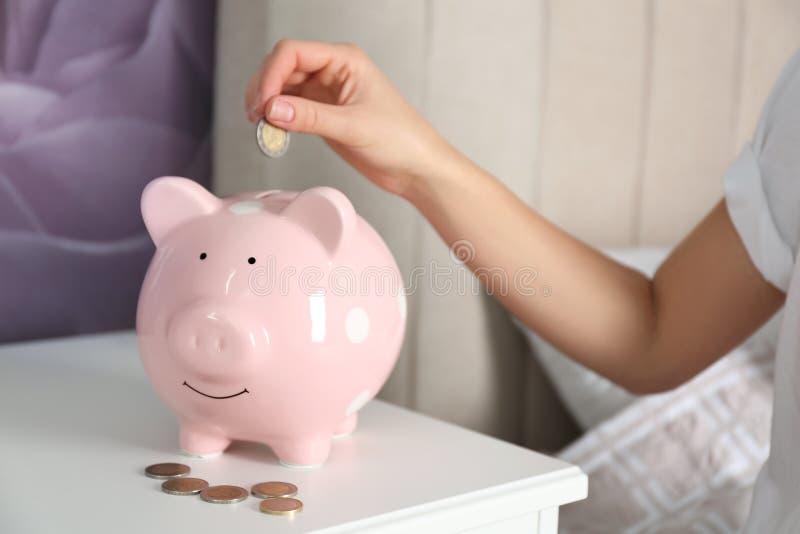 女人在床头柜把钱存入小猪库,特写 免版税库存照片