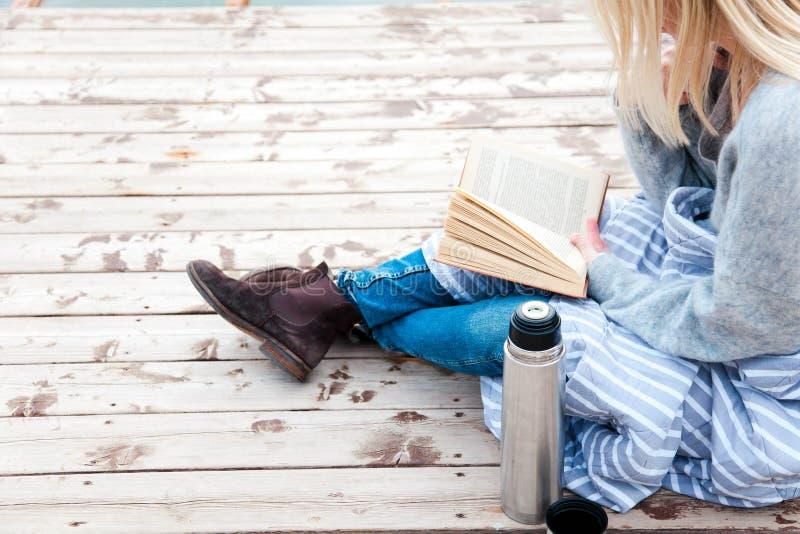 女人在秋海的木码头看书 舒适的秋日野餐,配有咖啡、热饮和茶 免版税库存照片