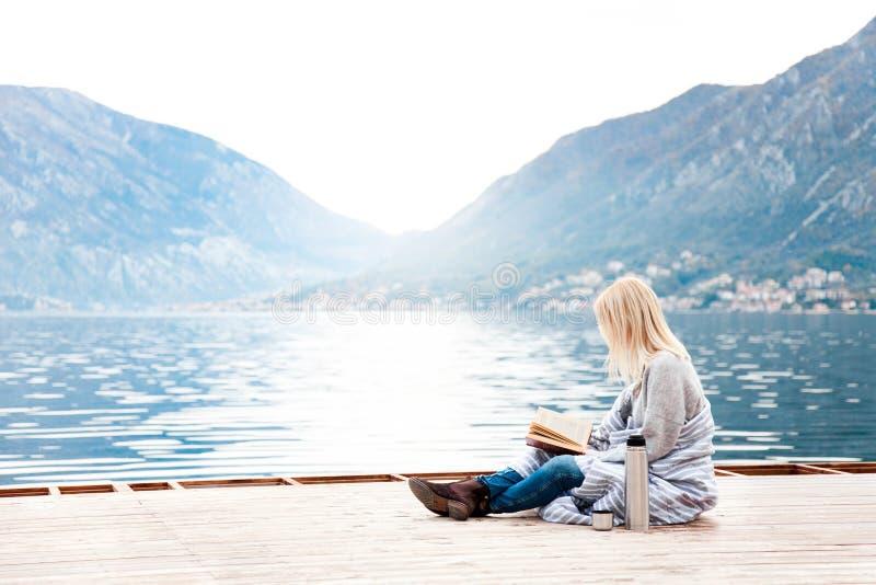 女人正在海边,山边,海滩的木码头看书 带咖啡的舒适冬季野餐 库存照片