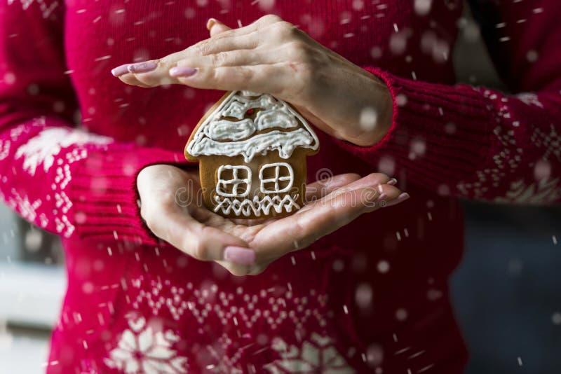 女人的手握着圣诞画的姜饼,形状为房子 图库摄影