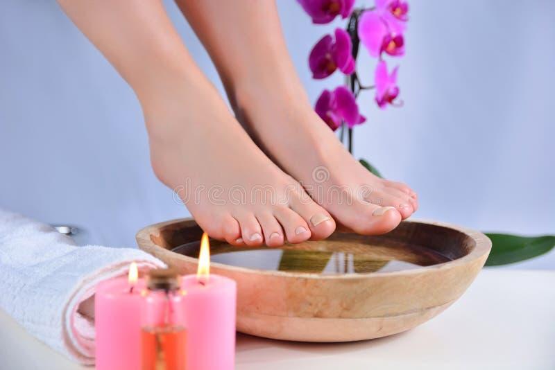 女人赤脚露在木碗上,有水和装饰性兰花 库存照片