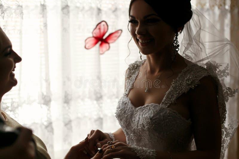 女傧相和新娘在屋子里握手 免版税库存照片