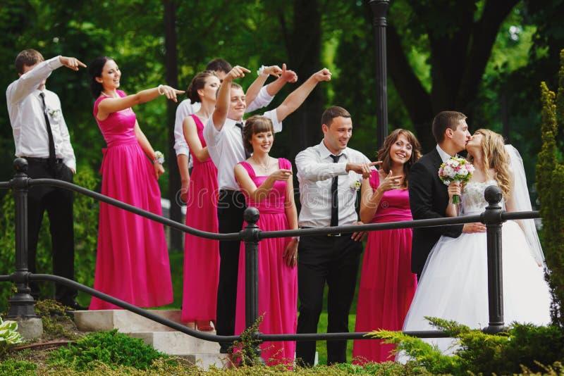 女傧相和男傧相凝视一对亲吻的婚礼夫妇 图库摄影