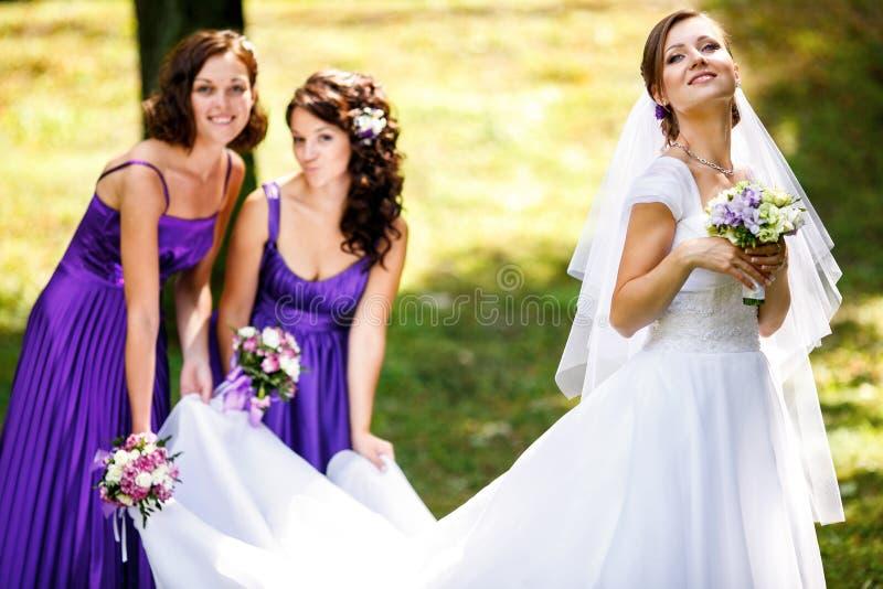 女傧相帮助新娘投入耳环和项链 库存图片