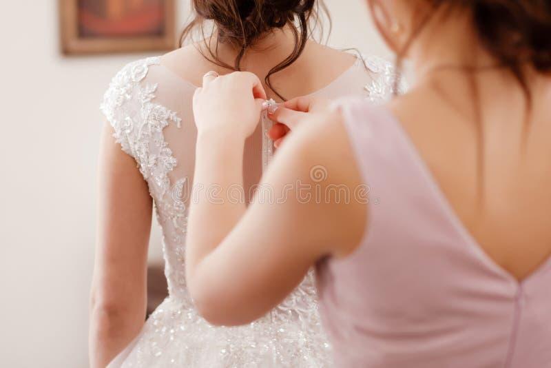 女傧相帮助的新娘紧固束腰和得到她的礼服,新娘在早晨为婚礼那天做准备 免版税库存照片