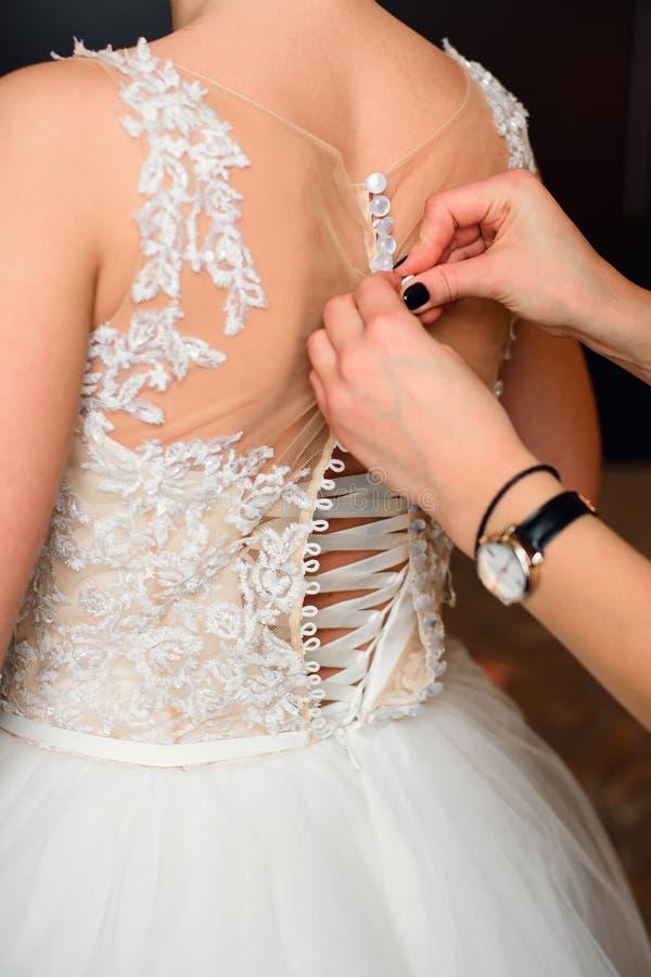女傧相手紧固按钮在婚礼礼服的新娘背面 免版税图库摄影