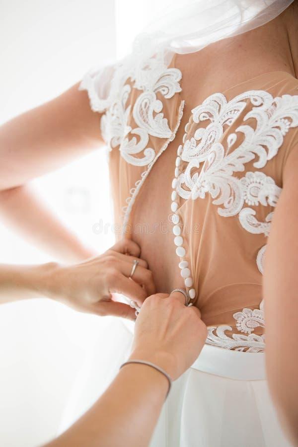 女傧相紧固在礼服的按钮在婚礼准备在早晨 图库摄影