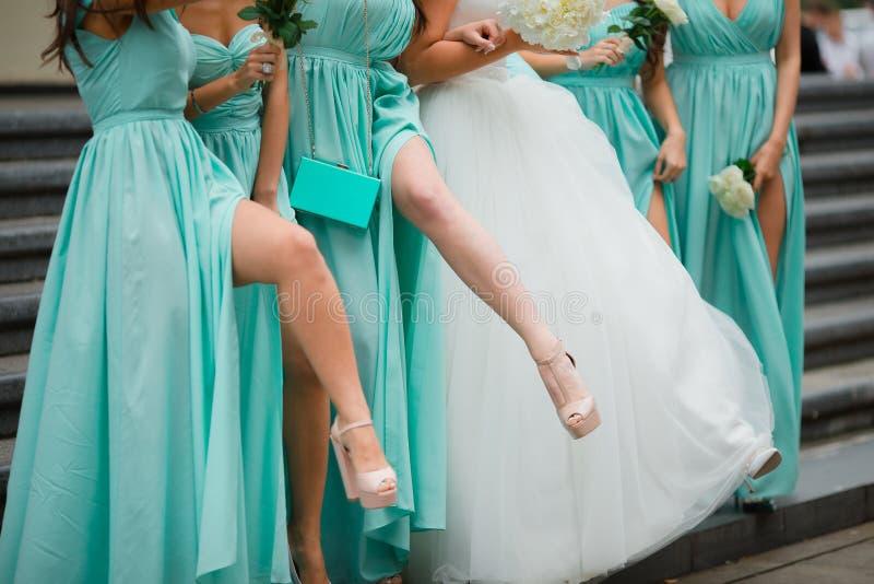 女傧相腿 穿戴在蓝色礼服 在台阶背景  免版税库存照片