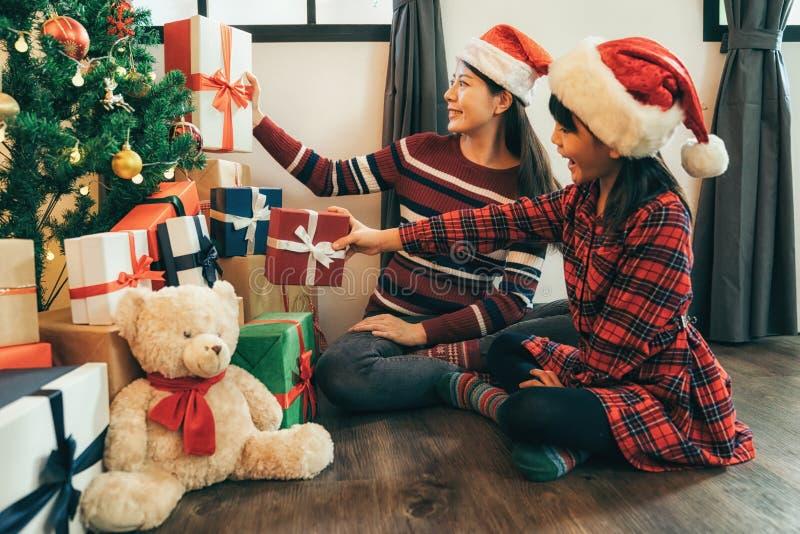 女儿和妈妈在圣诞树附近投入了礼物 免版税库存照片