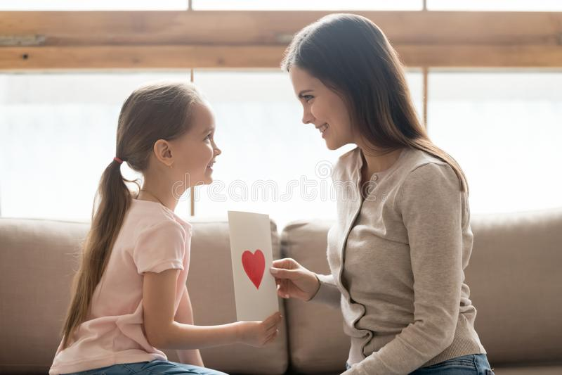 女儿和母亲坐拿着手工制造明信片的长沙发 免版税库存照片
