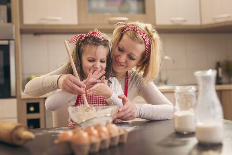 女儿和母亲揉的面团 免版税库存图片