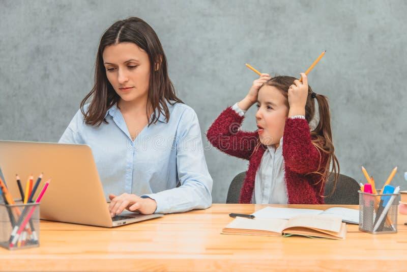 女儿和母亲灰色背景的 在此期间,女孩在她的头上把两只黄色蜡笔放,显示舌头 图库摄影