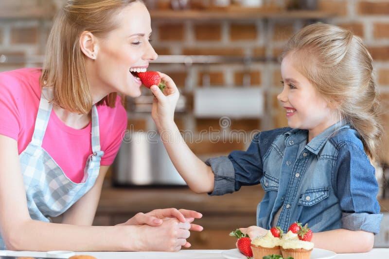 女儿哺养的母亲用从杯形蛋糕的草莓 免版税图库摄影