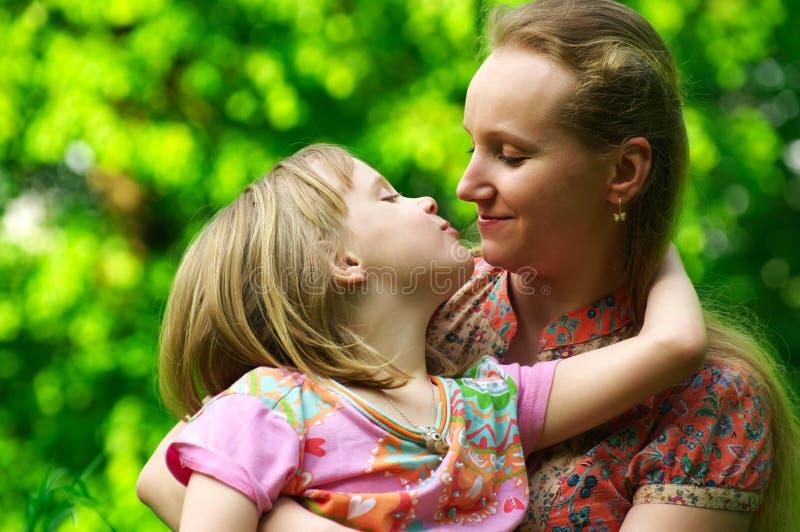 女儿她亲吻的妈咪 图库摄影