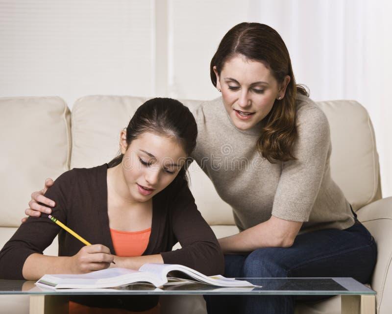 女儿帮助的家庭作业妇女 免版税库存图片