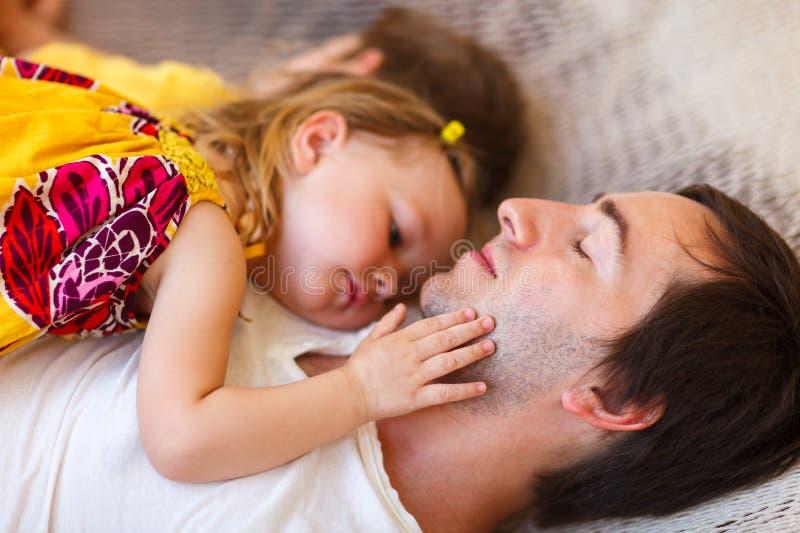 女儿放松父亲的吊床 免版税库存图片