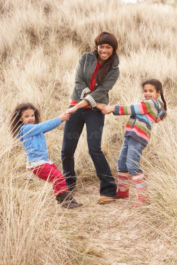 女儿有沙丘的乐趣母亲沙子 免版税库存图片