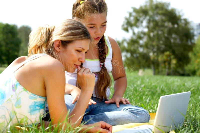 女儿滑稽的膝上型计算机妈妈 免版税库存照片