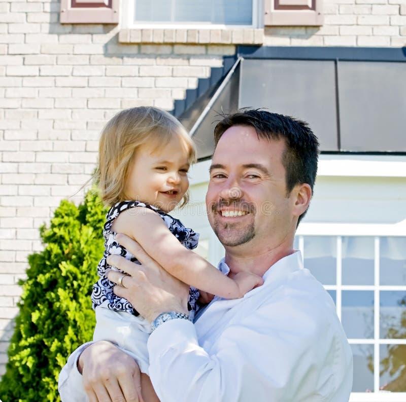 女儿父亲前面房子 库存照片