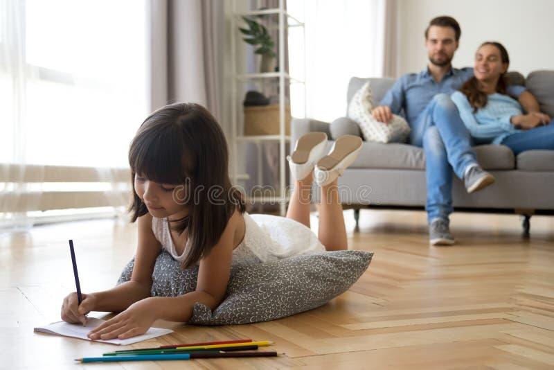女儿画说谎在温暖的地板父母坐长沙发 库存图片