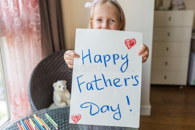 女儿祝贺爸爸并且给他礼物和明信片 愉快的父亲节概念 库存图片