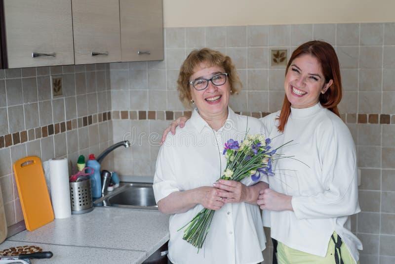 女儿给花一个成人母亲并且拥抱她在厨房里 : 库存图片