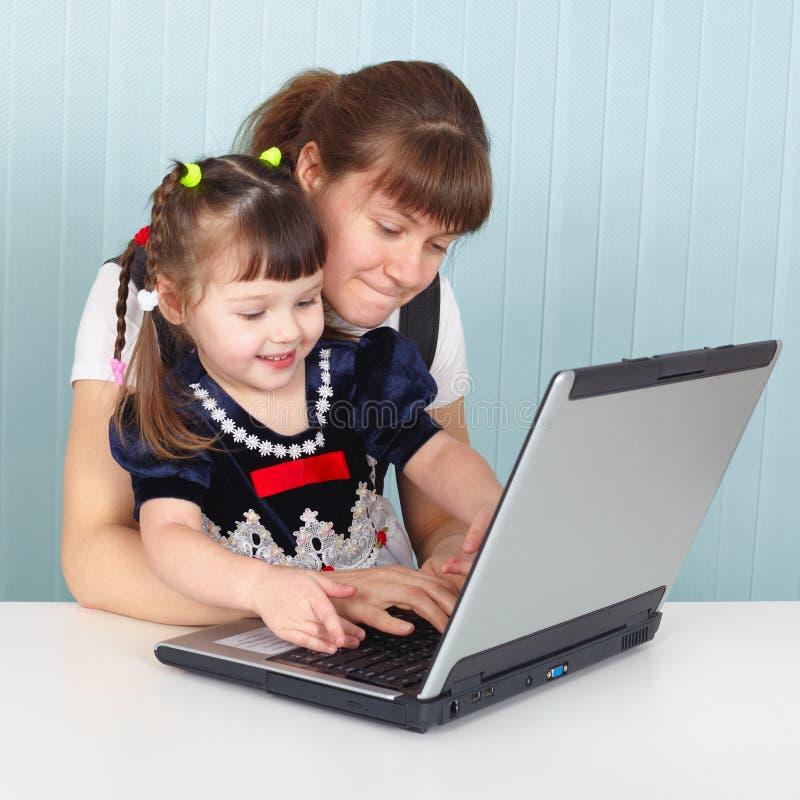 女儿膝上型计算机妈妈教使用 免版税库存照片