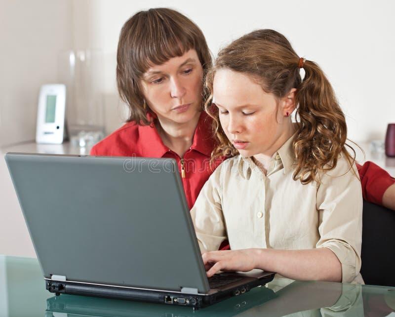 女儿膝上型计算机妈妈 免版税库存图片
