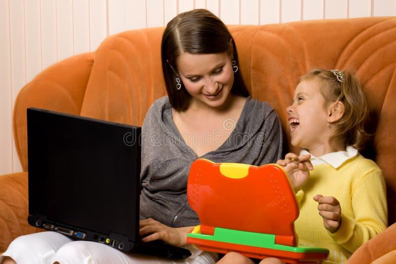 女儿膝上型计算机母亲使用 免版税库存照片
