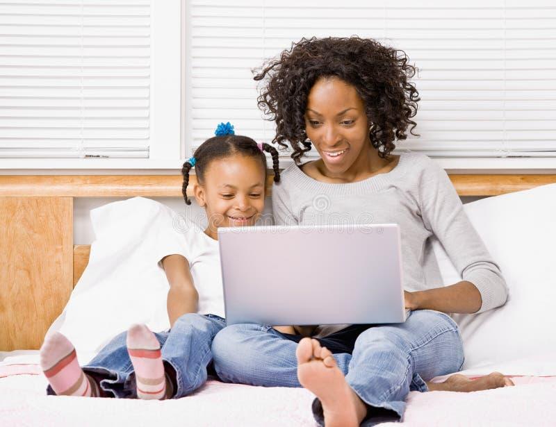 女儿膝上型计算机母亲键入 库存图片