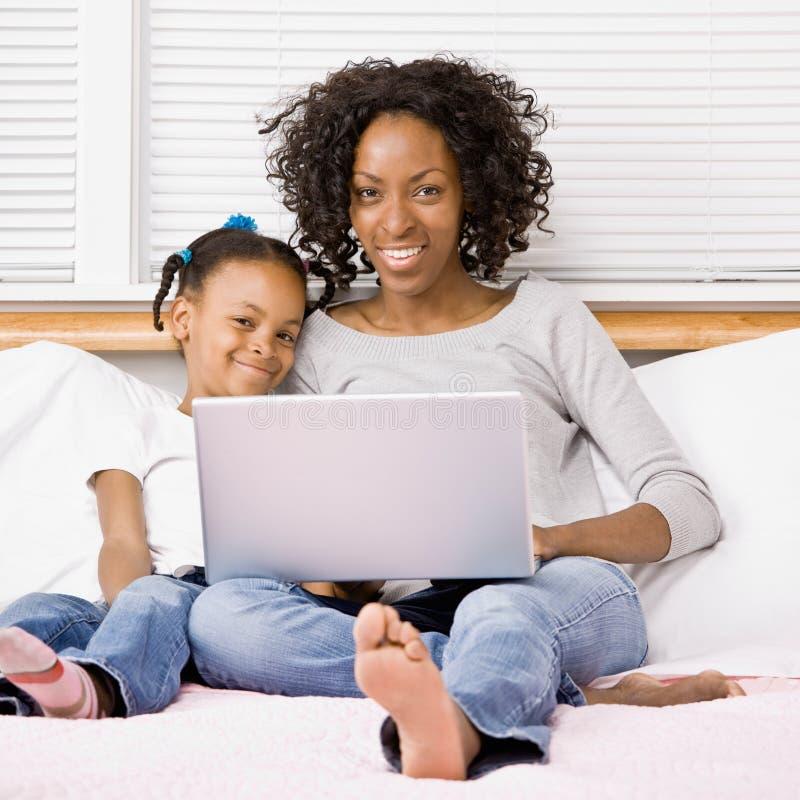 女儿膝上型计算机母亲键入 免版税库存图片