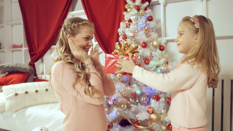 女儿给一件礼物她的母亲新年 免版税库存照片