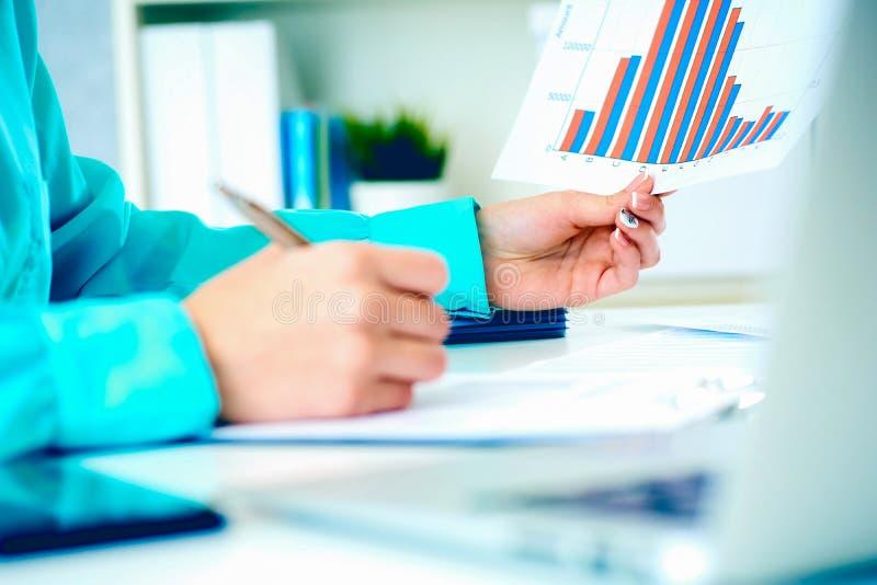 女商人与在手中拿着纸片与财政图的财务数据一起使用和做笔记  免版税图库摄影