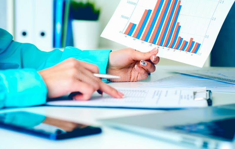 女商人与在手中拿着纸片与财政图的财务数据一起使用和做笔记  库存图片