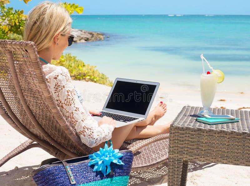 女商人与在海滩的计算机一起使用 库存图片