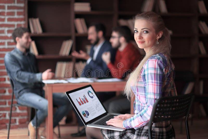 女商人与在膝上型计算机的营销图一起使用 在被弄脏的办公室背景的照片 免版税库存图片