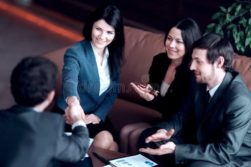 ?? 女商人与坐在工作书桌的商务伙伴握手 免版税库存照片