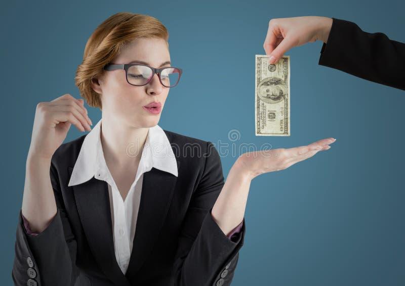 女商人与实施和有金钱的企业手反对蓝色背景 库存图片