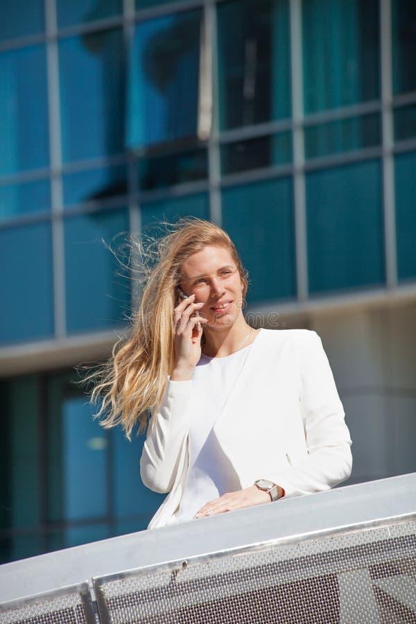 女商人与巧妙的电话一起使用在城市企业cen中 图库摄影