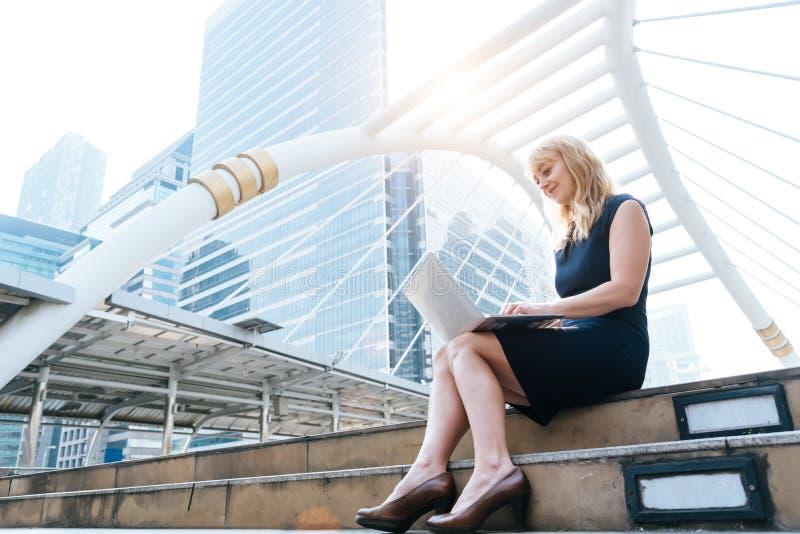 女商人与膝上型计算机一起使用在户外 技术和幸福概念 秀丽和生活方式概念 城市和都市 免版税库存照片